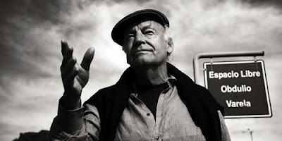 Eduardo Galeano, em preto e branco, em primeiro plano com a mão estendida, como se estivesse falando algo a alguém
