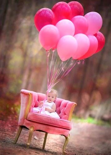 Niña sentada con globos rosas