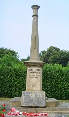 A tall white stone obelisk war memorial, with green hedges behind.