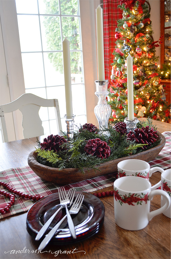 Dough bowl filled with wax dipped pine cones, greenery, and candles | www.andersonandgrant.com