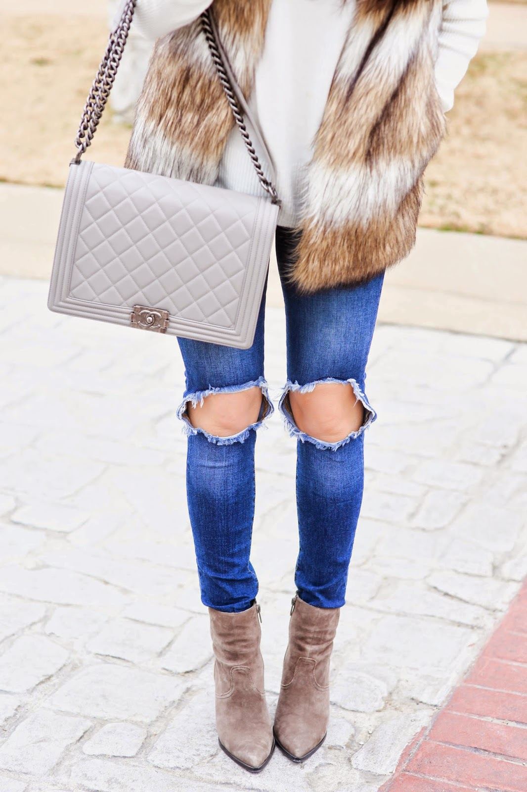faux fur vest, chic wish fur vest, ripped jeans, knee ripped jeans, grey chanel boy bag, the courtey bibb, bauble bar courtney bib with pearls, emily gemma, cream v neck sweater, michael hors runway watch in gold, david yurman black onyx ring, david yurman ring, ash jasmine booties