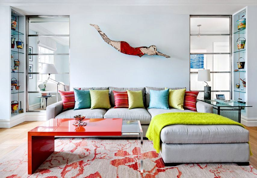 beach themed living room with folk art of a woman in a vintage swim costume diving on the wall, gray and red printed rug, gray sectional sofa with striped, turquoise and green accent pillows