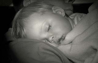 Kind schläft auf dem Arm