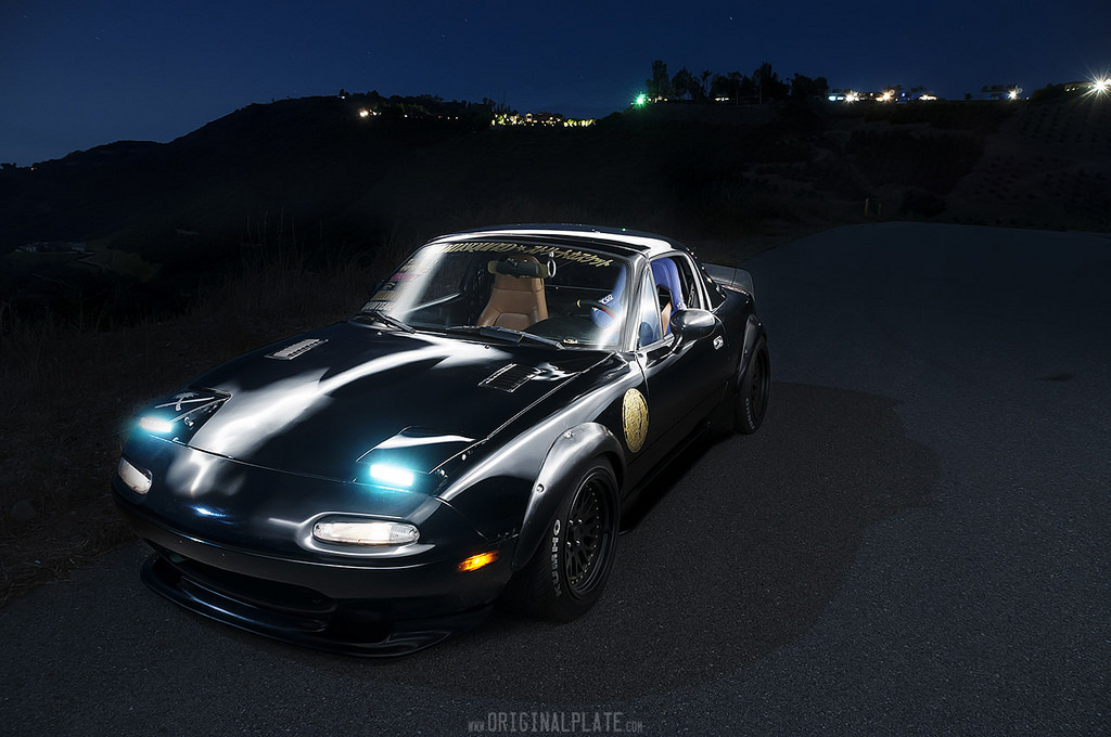 Mazda MX-5 z generacji NA, za oceanem znana jako Miata. To popularny i ceniony roadster. Samochód znany na całym świecie, rekordowa sprzedaż która trwa od 1989 roku pozwoliła mu objąć pozycję lidera w segmencie roadsterów. Zdjęcie nocą.