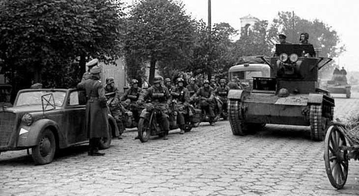 Советская танковая колонна проходит мимо группы немецких мотоциклистов