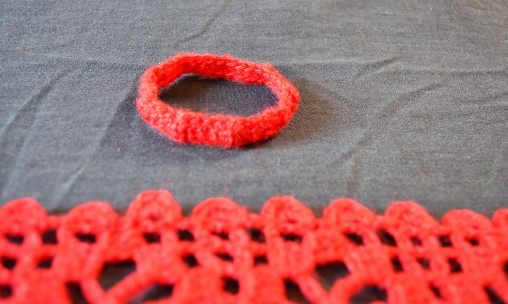 Close up of crocheted band which is used to fasten the ends of the scarf when worn. The band is the subject of the photograph and in focus. In the foreground is the scarf which is out of focus but the filet pattern in the body of the scarf and the scallop edging can still be seen.