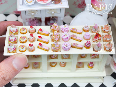 Individual pink pastries in 12th in a miniature pâtisserie setting - shown with hand for scale