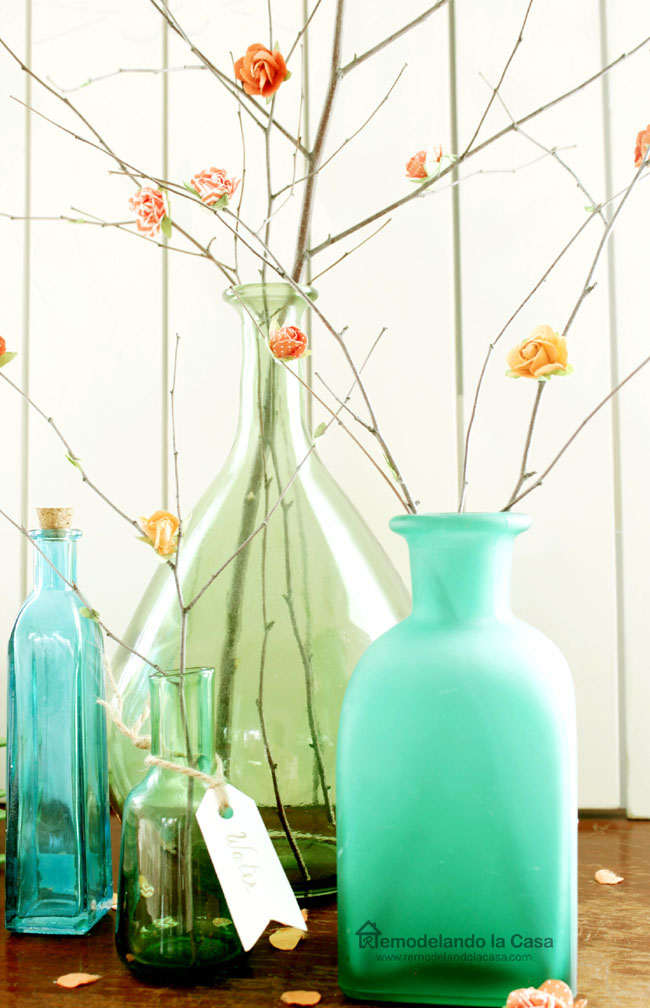 green and blue vases filled with branches with paper blossoms