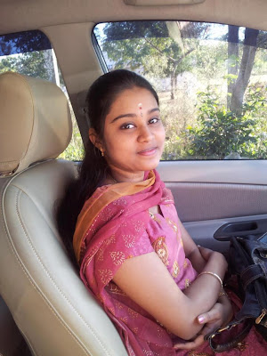 Homely Indian girl sitting inside car.