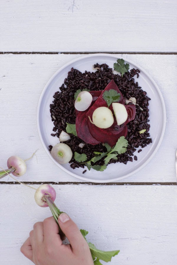 A plate with a black rice salad on a white background