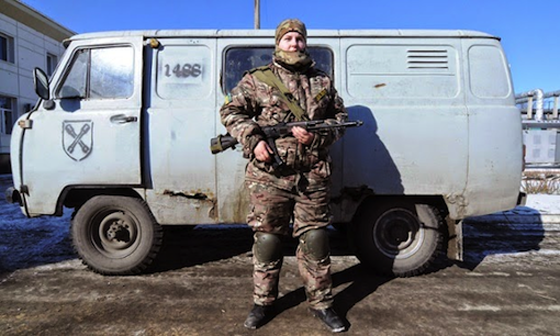 Female soldier fighting for Ukraine's post-coup government stands in front of a van with a German Waffen SS insignia  and a neo-Nazi code number.