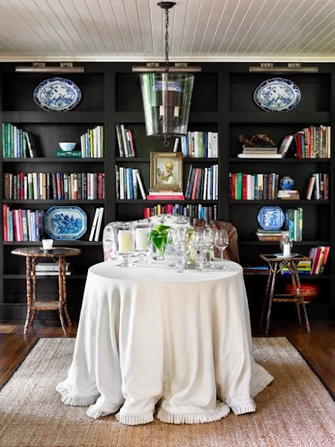 black bookcases in library with skirted table