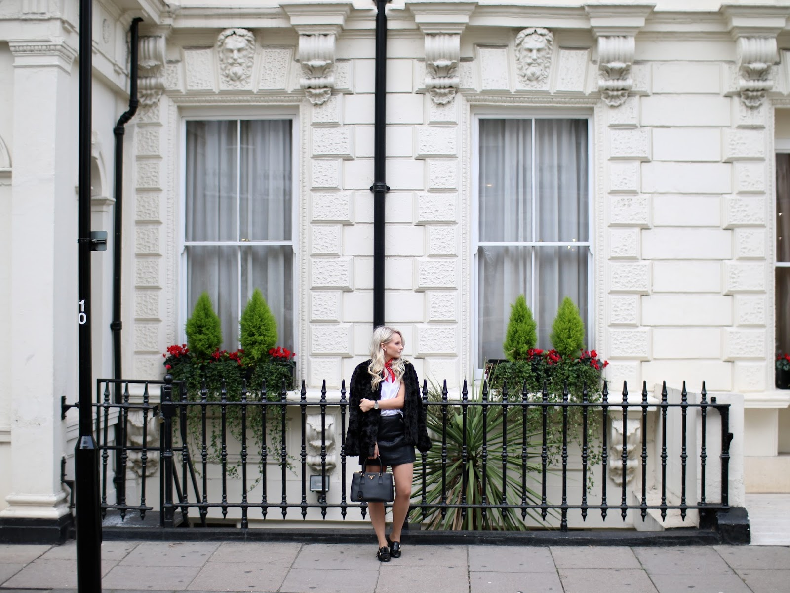 a women in front of beautiful building in London, green and red flowers behind her, she is wearing a dark coloured fur coat