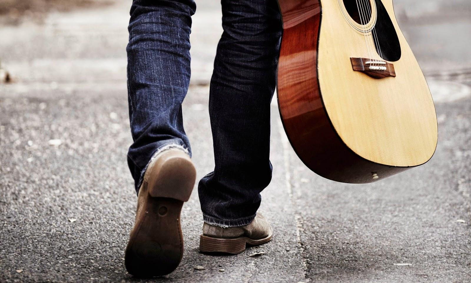 Menyandang gitar dan bernyanyi