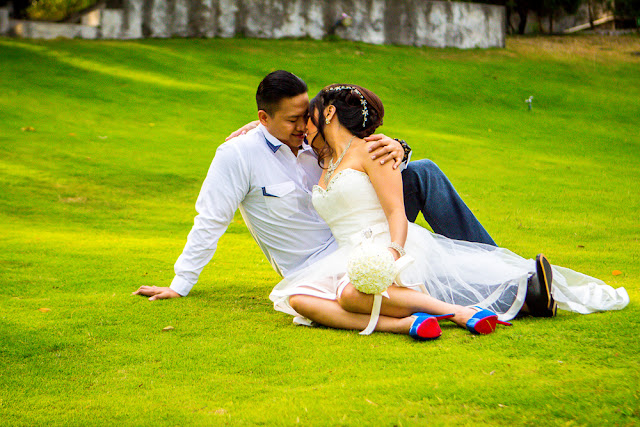 foto prewedding romantis dengan gaun pendek dan kemeja putih di atas rerumputan hijau, lokasi di kalyana resort kaliurang yogyakarta