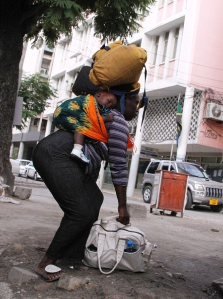 A woman struggles to pick up a bag while she balances the load she is already carrying with a baby on her back as captured along Samora Avenue in Dar es Salaam Saturday. (Photo by Mohamed Mambo)