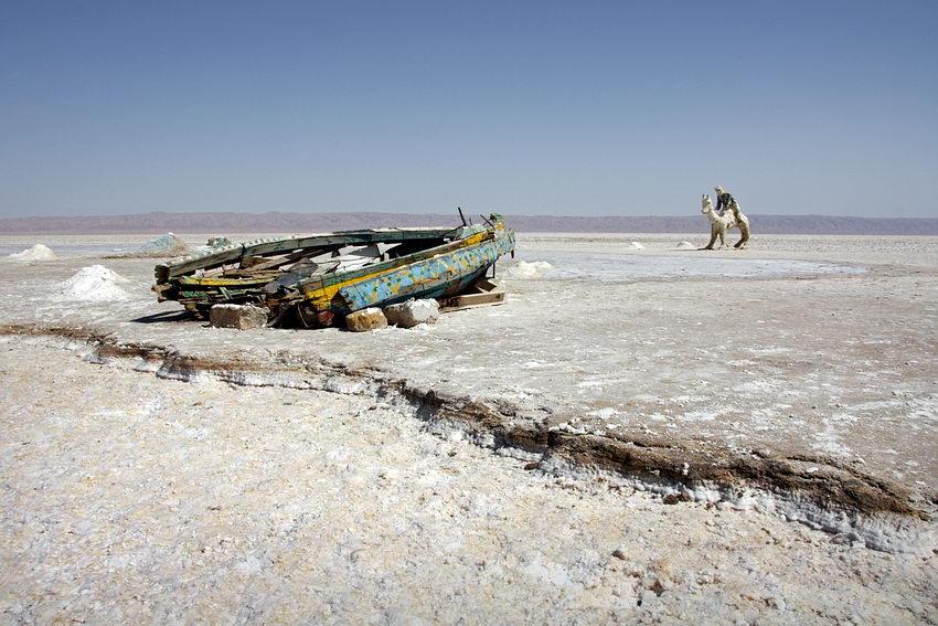 Paisagem do lago seco com os restos de um barco à esquerda e um camelo com cavaleiro, feitos de sal, à direita