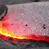 A man steps on glowing hot lava to demonstrate something