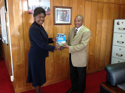 Hon. Charity Ngilu Minister for Water and Irrigatiuon  receives the SME Handbook