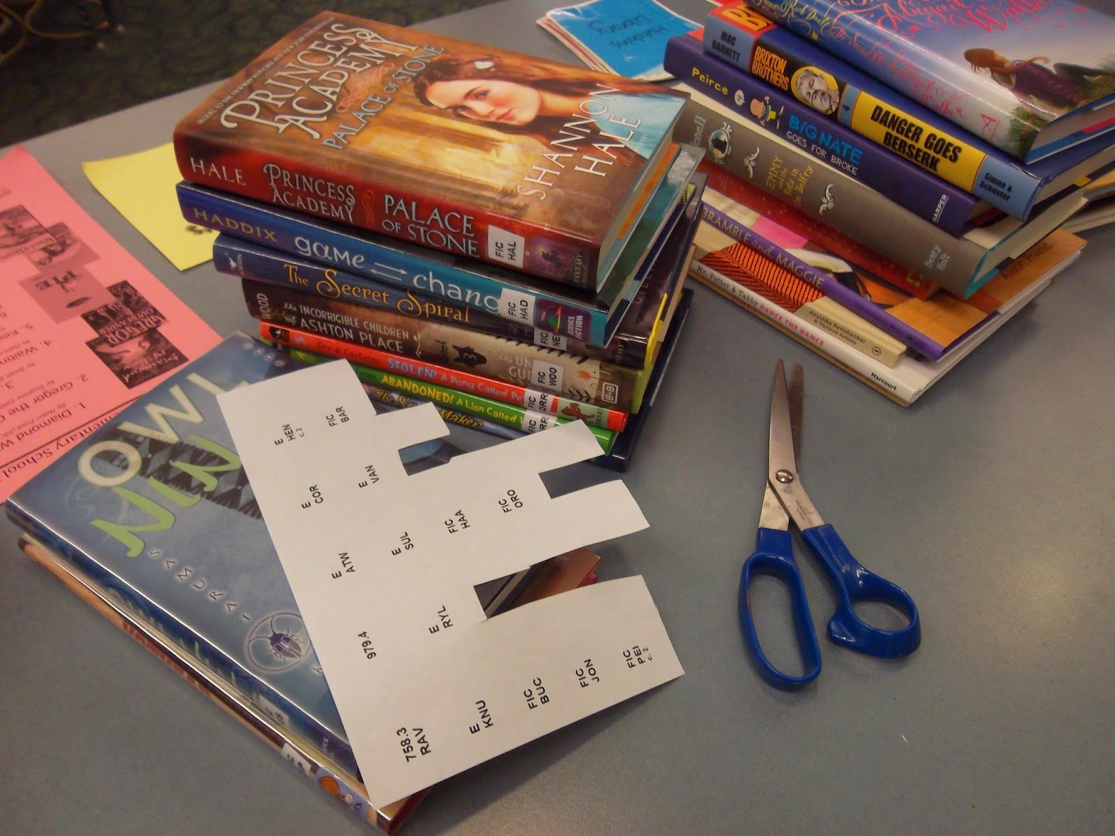 Several stacks of books, some with spine labels and others waiting to have labels placed on them. A paper print-out of spine labels is in the foreground with a pair of scissors
