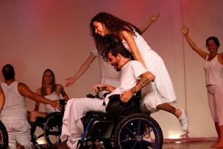 Léo e Bia - Guilherme Rocha, ator cadeirante (tetraplégico) corre sorridente pelo palco em sua cadeira motorizada, levando Sara, também sorrindo, de pé na parte de trás da cadeira.