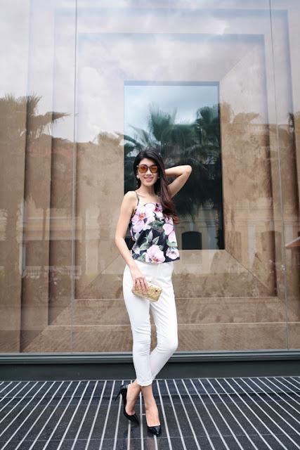 Áo hai dây in hoa được phối cùng quần ôm ống lửng trắng mang lại nét năng động và gợi cảm.