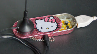 [Image: Photo of a very small radio hotglued inside a Hello Kitty branded tin.]