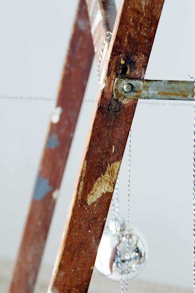 Detailblick auf eine Holzleiter mit Weihnachtskugeln im Hintergrund