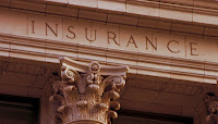 "Photo of old classical style building with ""Insurance"" carved on its facade"