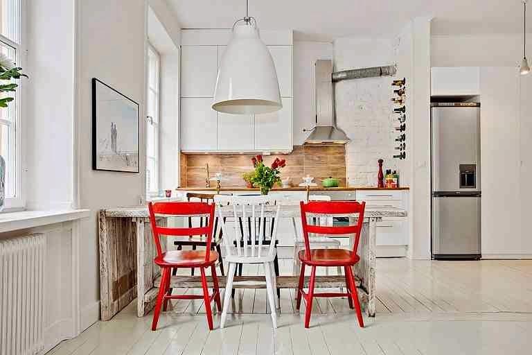 Biała kuchnia, czerwone krzesła, białe krzesło, drewniany stół, białe meble kuchenne