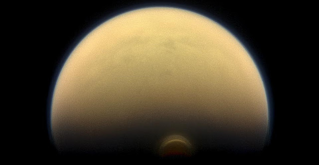 """As winter sets in at Titan's south pole, a cloud system called the south polar vortex (small, bright """"button"""") has been forming, as seen in this 2013 image. Image Credit: NASA/JPL-Caltech/Space Science Institute"""