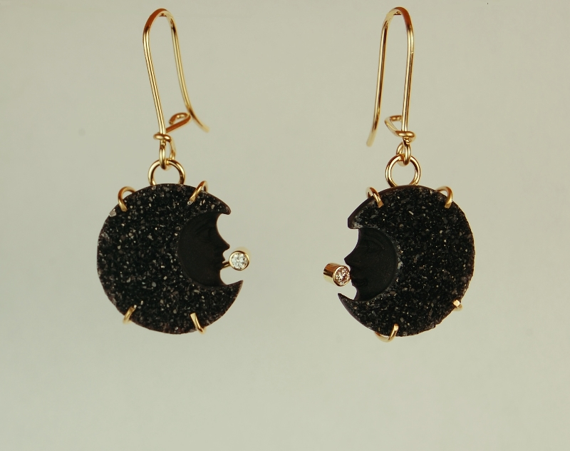 Black sparkly gem stones with carved moon face in them and diamond earrings