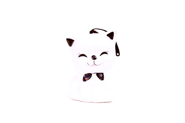 photo of smiling white cat with black accents and bow tie