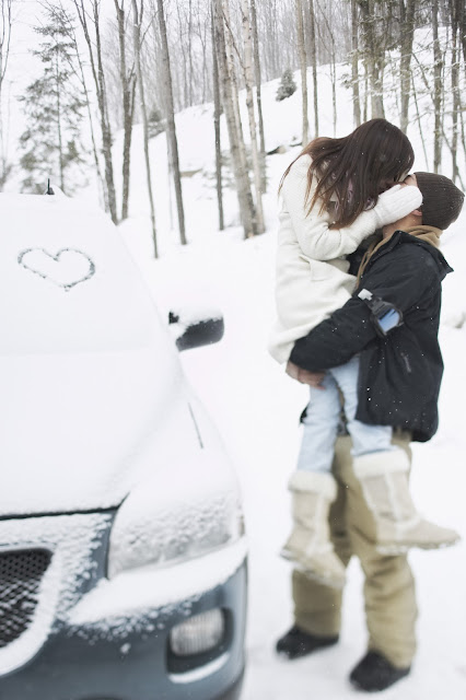 Woman held in her lover's arms, kissing on a snowy mountain.