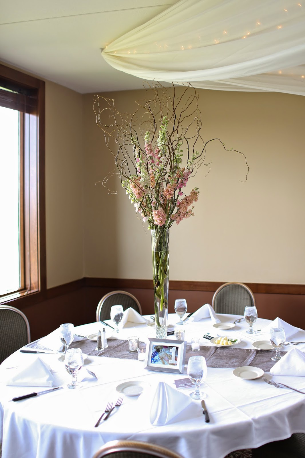 Forget me not floral events march 2015 the third style was a tall arrangement in a pilsner vase of curly willow larkspur and stock in pinks whites and corals again with silver table runners reviewsmspy