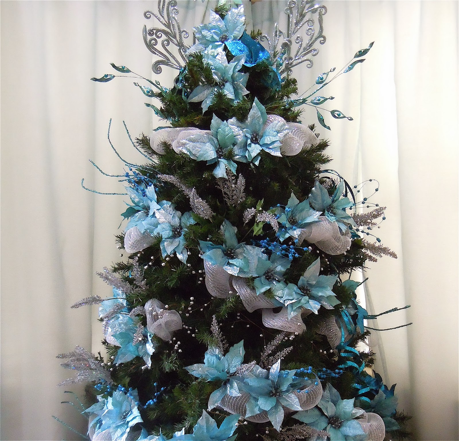 still in the initial stages of decorating just with turquoise poinsettias silver and blue picks no ornaments yet and it looks full already
