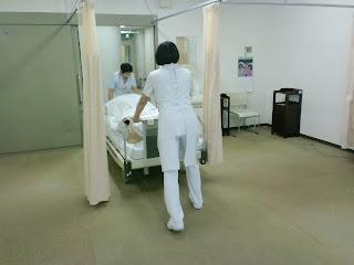 写真:ベッドを押して病室から出ていこうとする看護師さん