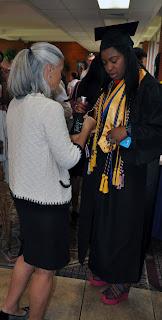 Adjunct Professor Cutty Gilbert helps prepare a student for graduation.