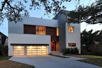 fachada de casa moderna blanca con cochera iluminada
