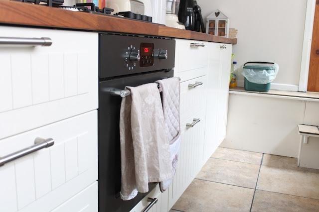 cream cottage style IKEA kitchen with walnut worktop and black appliances