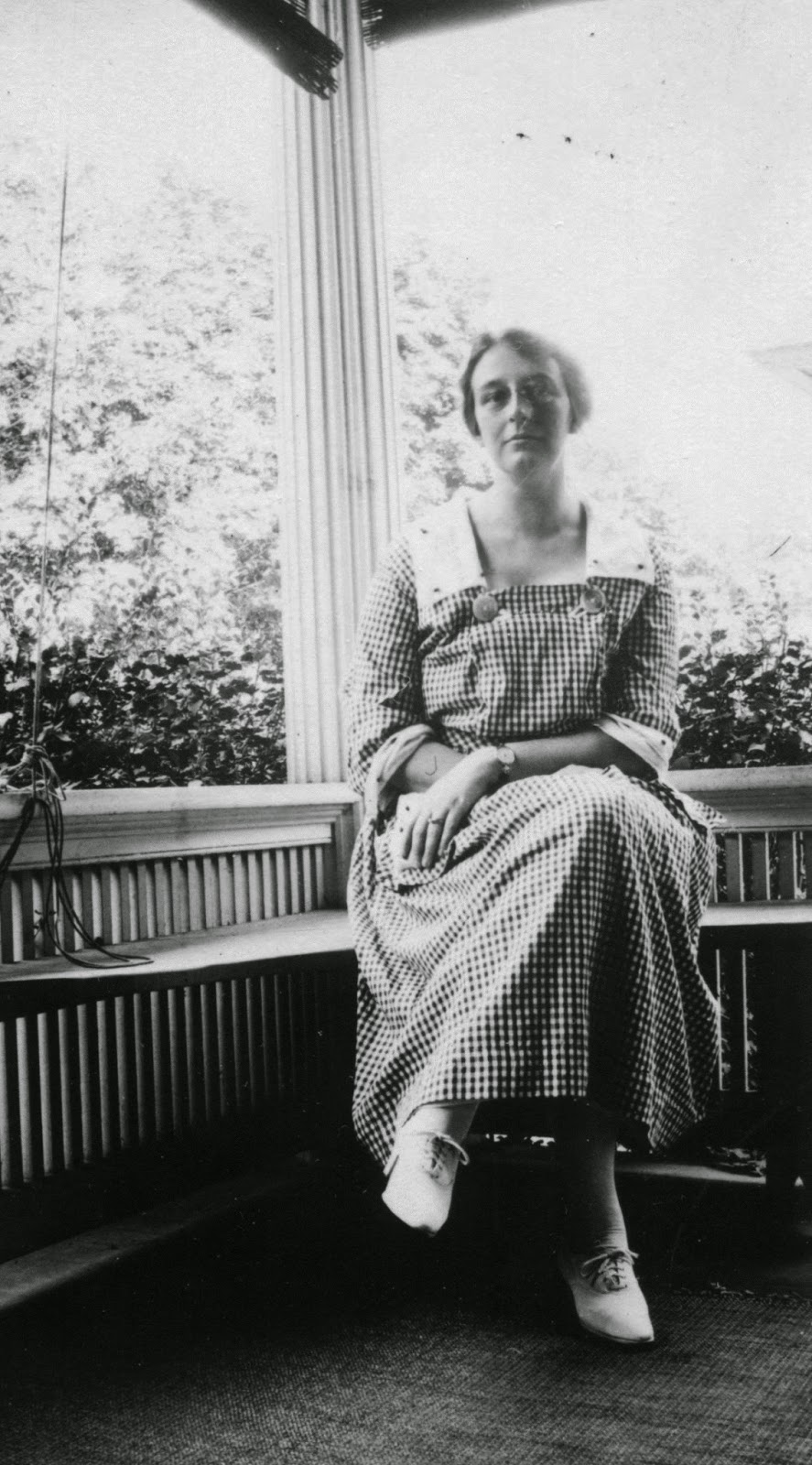 Photo of a young woman sitting on a porch, c. 1920