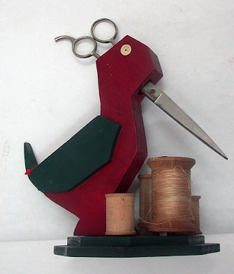 red wooden bird holding scissors, with spools of thread on the base