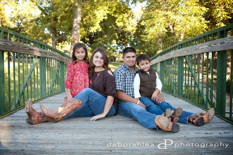 Family of 4 sitting on a bridge wearing cowboy boots.