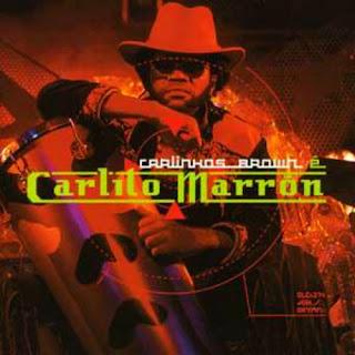 """Capa do álbum """"Carlito Marrón"""", lançado por Carlinhos Brown em 2003. Brown aparece com chapéu de cowboy e um timbal, na capa."""