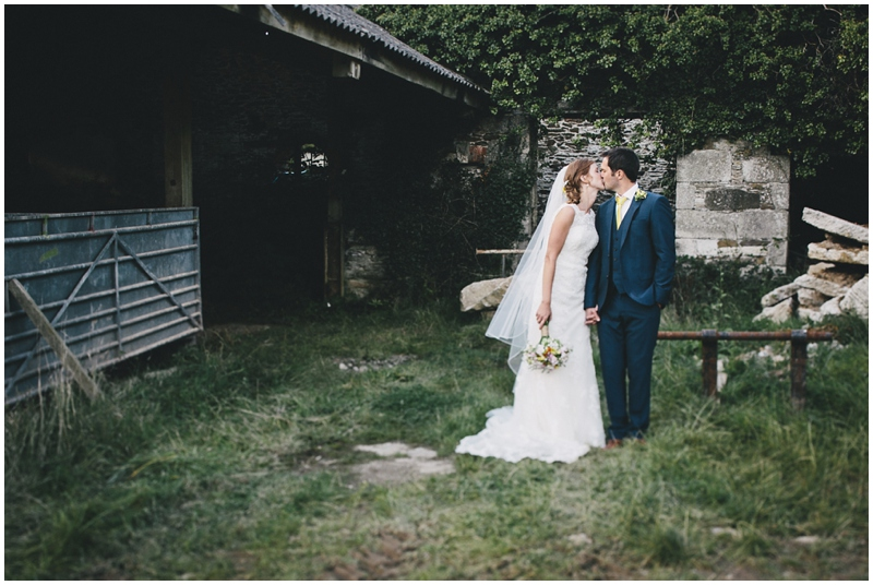 Bride and groom kissing near barn on farm