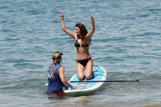 Ali Landry sitting on a paddle board in a black bikini with her hands up