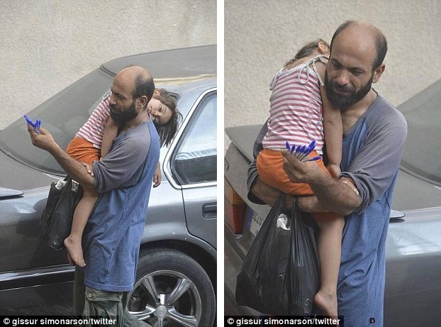 The Pen Is Mightier Than The Sword: Touching photo of desperate refugee selling biros in Beirut street as he carries his sleeping daughter.