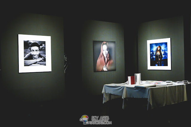 Huge portraits hanged on the wall and photobooks on the table