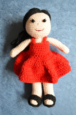 The AKA Amigurumi project. A little doll with straight black hair, black button eyes with eyelashes, a red dress and black sandals.