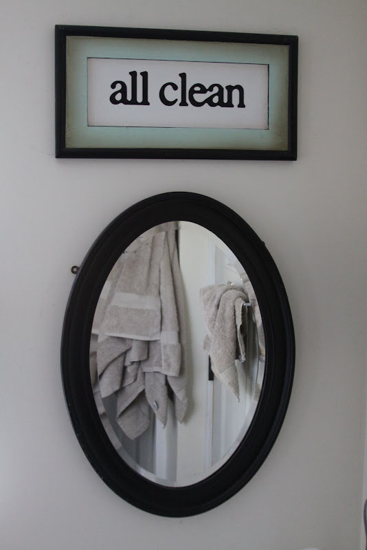 Vintage beveled mirror reflecting bath towels. title=